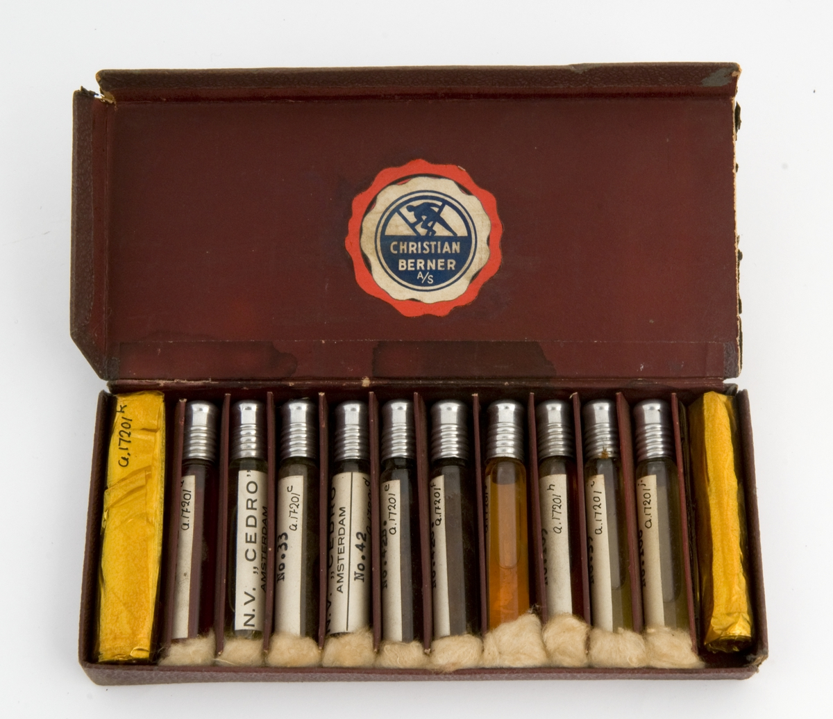 Medisineske av papp trukket med burgunder skinnimitert papir. Inneholder10 glassampuller med essenser og to ruller med gullfarget cellofan.